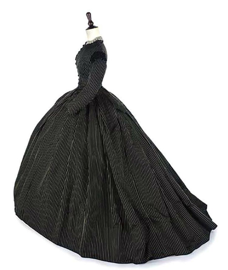 Two-piece daytime gown in black & white stripe, 1860s. High-necked, boned bodice closes with row of black jet-trimmed buttons and with vestigal tails at back waist. Full skirt, designed to be worn with crinoline, is slightly trained. Christie's