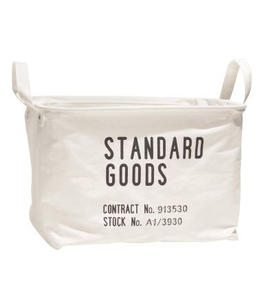 White. Storage basket in thick fabric with printed text motif. Double handles, concealed metal edge at top for stability, and plastic-coated inside. Size 9