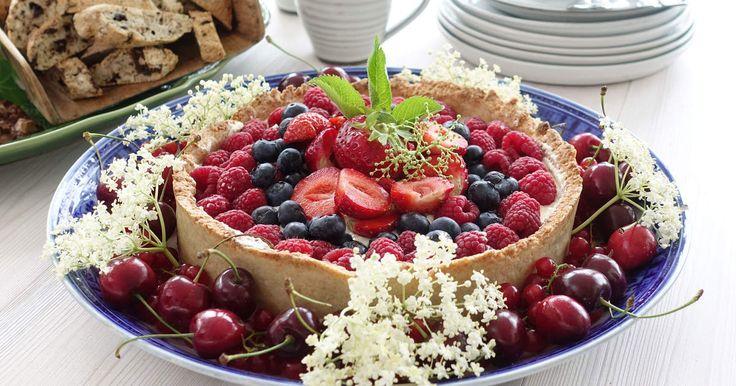 En sommartårta lika vacker som god! Du gör tårtbotten på riven mandelmassa, en krämig fyllning med apelsin och fläder och toppar med grädde och färska bär.