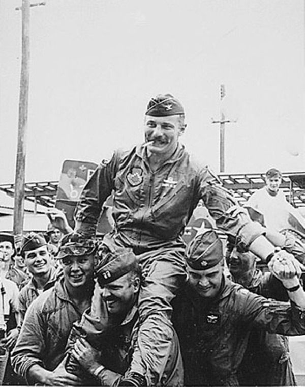 Photograph of Colonel Robin Olds Being Carried Away From His F-4 Phantom II After His 100th Combat Mission Over North Vietnam. (NATIONAL ARCHIVES PHOTO)