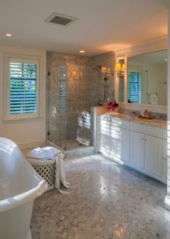 A large mosaic floor pattern in this bathroom carries through into the shower