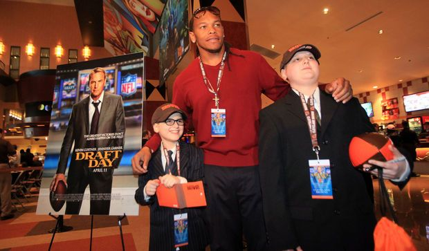 "Cleveland Browns Jabaal Sheard poses for a photo with Lucas Miller, 9, and brother Frank Miller III, 13, while walking the orange carpet during the movie premier of ""Draft Day."" The brothers are from Brook Park and were special guests for Littlest Heroes, an organization t for children with cancer. Frank has Leukemia. (Joshua Gunter/ The Plain Dealer)"