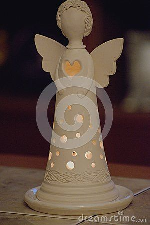 Candle holder angel figurine with candle.