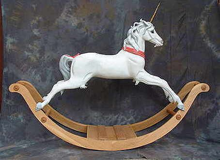 An unusual rocking Unicorn with carved mane and tail and a carved pink sash. Also available with horse hair mane and tail and different colour schemes..