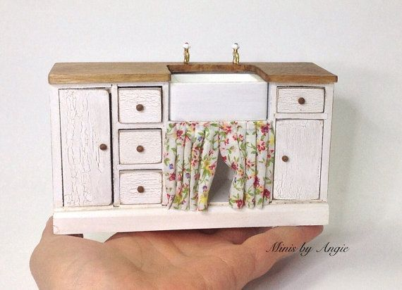This is a 1/12 scale dollhouse miniature. Kitchen sink unit made of wood. Painted in white and distressed. All the cupboard doors and drawers open.