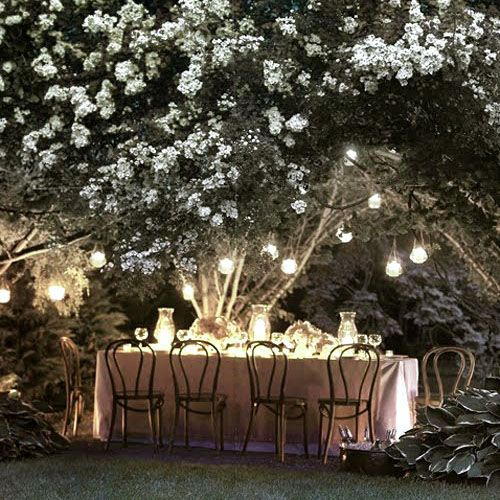 Dining outdoors at night is magical under lighting and white flowers, from Arcadian Home.
