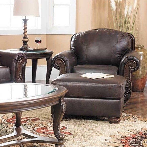 Bring traditional warmth and coziness to your home with the Mellwood Walnut Leather Collection by Ashley Furniture. Rolled arms carves bun feet and showood details with classic botanical designs give this chair its rich traditional character. Shop in stores or online at afw.com.