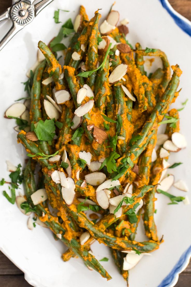 Easy summer roasted green beans topped with a homemade romesco sauce (roasted red pepper/almonds) and topped with extra almonds and fresh parsley.