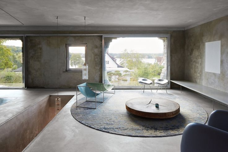One of the living-room spaces, with a table made of Persian ironwood, and chairs by Muller Van Severen (left) and the Japanese architecture firm SANAA. The windows offer a view of the lake and the neighboring houses.