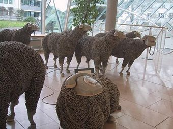 Recycled telephone and phone cords--sheep made out of phone cords with telephones for heads.
