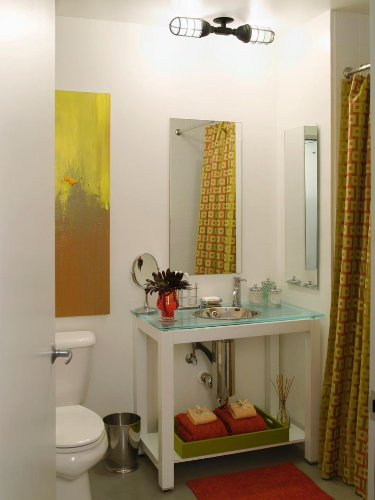 Scale is an important element to consider when choosing a bathroom mirror. In this bathroom by Lori Dennis, a vertical mirror works together with the long shower curtain and painting to lengthen the feel of a small bath.