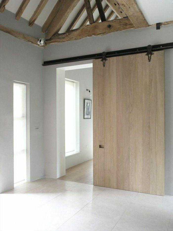 une belle porte en bois coulissante, plafond sous pente, mansardé, chambre avec beaucoup de lumière
