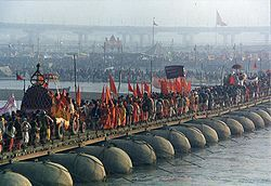 A procession of Akharas marching over a makeshift bridge over the Ganges river, Kumbh Mela at Prayag, 2001
