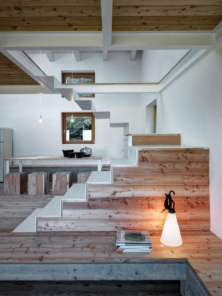 La scala, oltre a servire da collegamento tra i piani, divide la zona giorno e ospita un piccolo armadio.