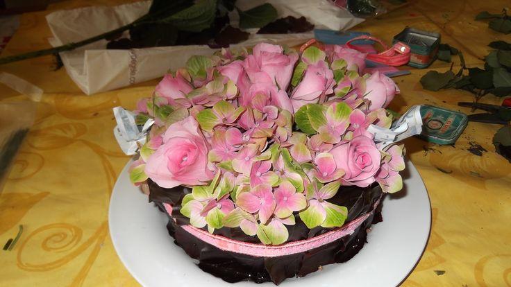 """een bloemen """"taart"""" met geld verstopt tussen de bloemen."""