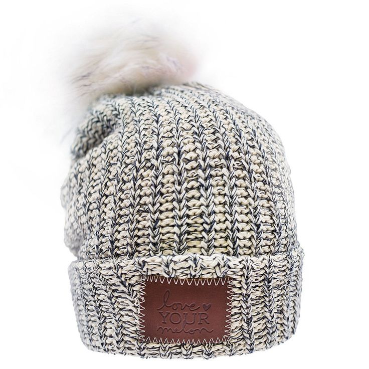 This pom beanie is knit out of 100% cotton yarn in natural and navy colors. It features a brown leather patch that is debossed with the Love Your Melon logo and a detachable, white faux fur pom. Made