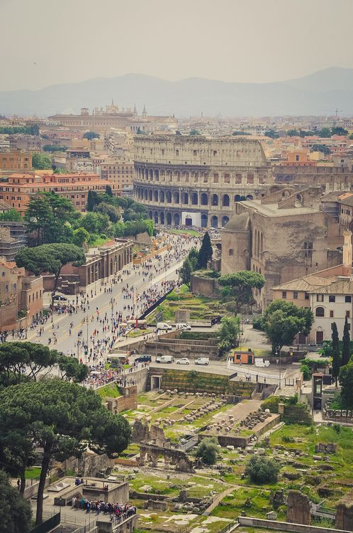 Rome, Italy by Alex Cocian. This is a good shot of the Via dei Fori Imperiali. The main characters watch a parade from the left side of this street early in the book.