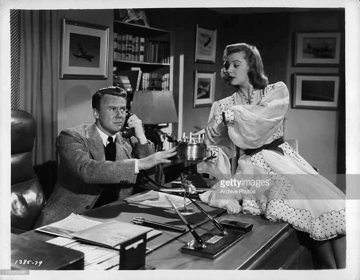 Van Johnson on the phone as June Allyson is sitting on the desk in a scene from the film 'High Barbaree', 1947.