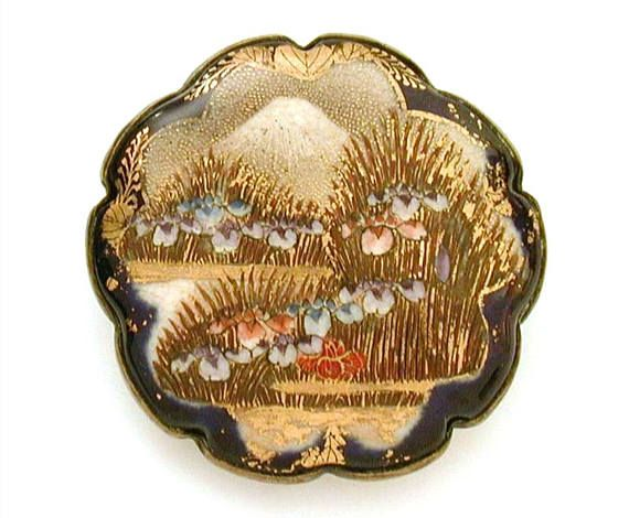Een mooi voorbeeld van antieke Japanse aardewerk, deze grote Satsuma-broche beeltenis van Mt. Fuji met iris bloesems en gebladerte op de voorgrond.  Het heeft de kenmerkende crème kleur en fijne craquelé in het glazuur. De geschulpte rand is kobalt blauw. Goud glazuur was royaal toegepast op Cinnaber kleuren. Verschillende blues, paars en oranje ook weergegeven.  Zoals gezegd, is de pin vrij groot op amper 2 in diameter. Een c-gesp beveiligt het juweel.  De achterkant is gestempeld met het…