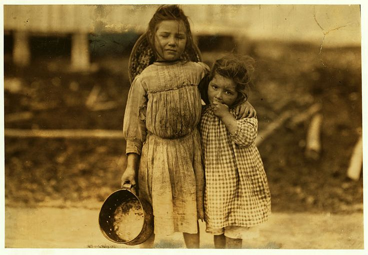 Maud Daly, five years old. Grade Daly, three years old. Each picks about one pot of shrimp a day for the Peerless Oyster Co. The youngest said to be the fastest worker. Location: Bay St. Louis, Mississippi. Photograph by Lewis Wickes Hine, March 1911.