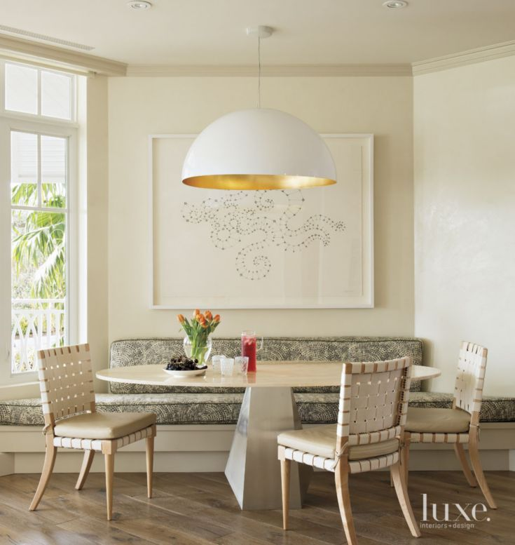 A custom banquette provides window-side dining in the breakfast area; the cushions, fabricated by Associated Interior Designer Service, wear a calvin fabrics textile from Donghia. Woven Niedermaier chairs surround a table from Egg Collective in Brooklyn, while a large half-dome light fixture—by Oluce from DDC—provides nighttime illumination. Amy Lin's pencil-on-paper is from Addison/Ripley fine art in Washington, D.C.