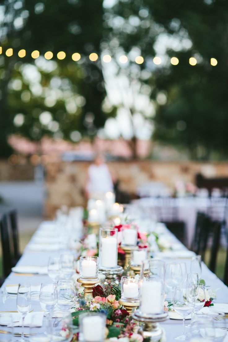 pale grey linens are the perfect choice for this wedding head table filled with a mixture of gold and silver mercury glass pedestals and candles set along a lush garland of mixed greenery filled with burgundy, pink, blush, peach and white flowers and vines.