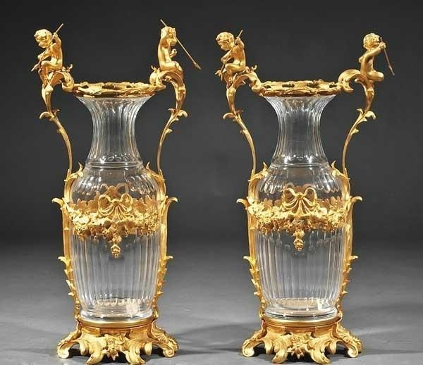"""Magnificent Pair of Very Heavy Palacial and Museum Quality Pair of Louis XV Style Gilt Bronze Mounted Crystal Urns, the fluted body with floral festoons, foliate handles surmounted by Cherub like figures holding Pitchforks on each side, raised on rocaille and floral bases. 34.5""""H x 17""""W."""