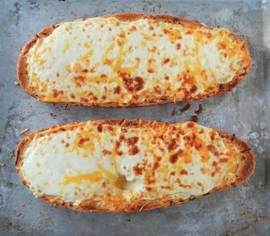 Чесночный хлеб с сыром Ингредиенты: 1 буханка французского хлеба, разрезать вдоль напополам 5 столовых ложек размягченного сливочного масла 6 зубчиков чеснока, выдавить 1,5 стакана тертой моцареллы 1 стакан тертого чеддера Приготовление: Нагрейте духовку до 230 градусов. Масло смешайте с чесноком и намажьте его на хлеб. Сверху присыпьте смешанными двумя видами сыра и отправьте выпекаться на 4-8 минут.