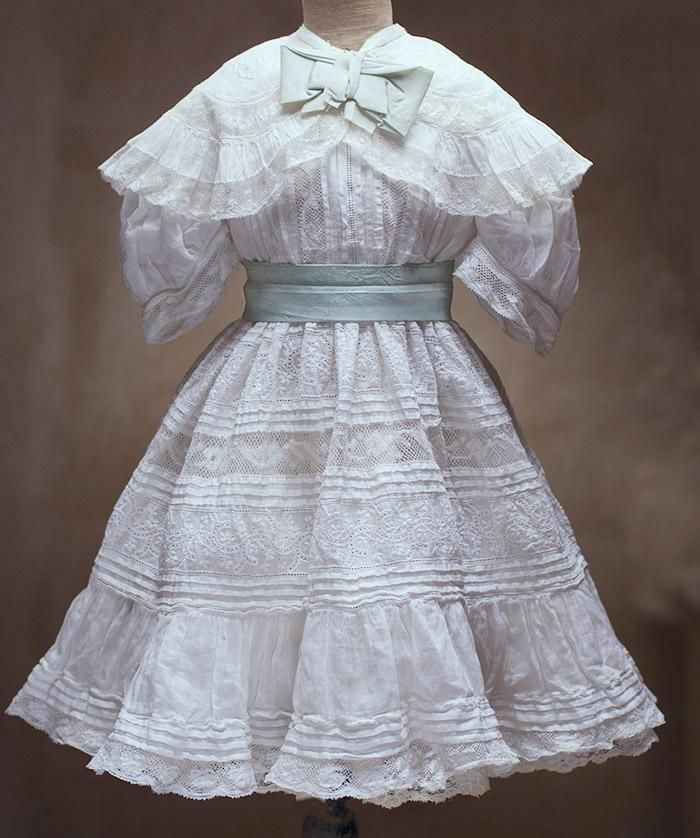Very beautiful dress has rounded neckline, 3/4 sleeves with lace edging lace, wide collar with white embroidery and lace edging, open work and white