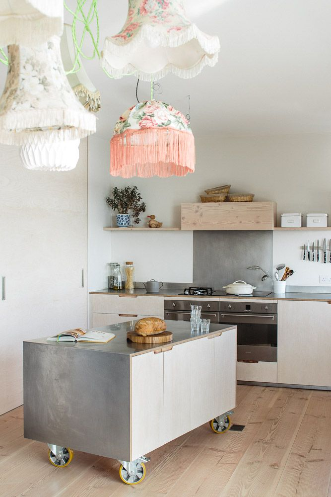 Moveable kitchen island on industrial castors finished with brushed stainless steel and exposed lye-treated plywood and routed cabinet pulls.There are sunken sockets on the Dinesen Douglas Fir flooring for appliances.