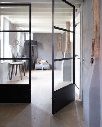 Een donkere hoek wordt een lekker lichte ruimte door de dichte (stal)deur te vervangen door een strakke glazen taatsdeur - een deur zonder posten, die 'los' in de ruimte draait door bevestiging onder en boven.