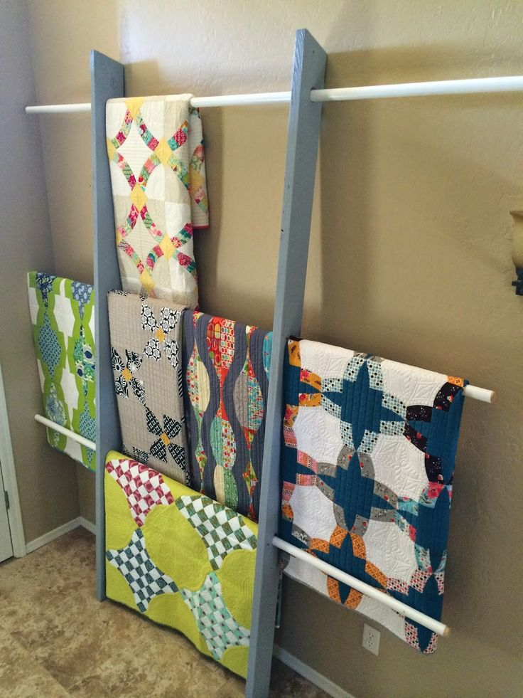 """build a quilt rack (2) 2""""x6""""x8' (sanded and painted) (3) vinyl coated closet doweling (Home Depot) 1 1/2"""" holes drilled 31"""" apart 1/4"""" angle cut at top and bottom for looks and functionality"""