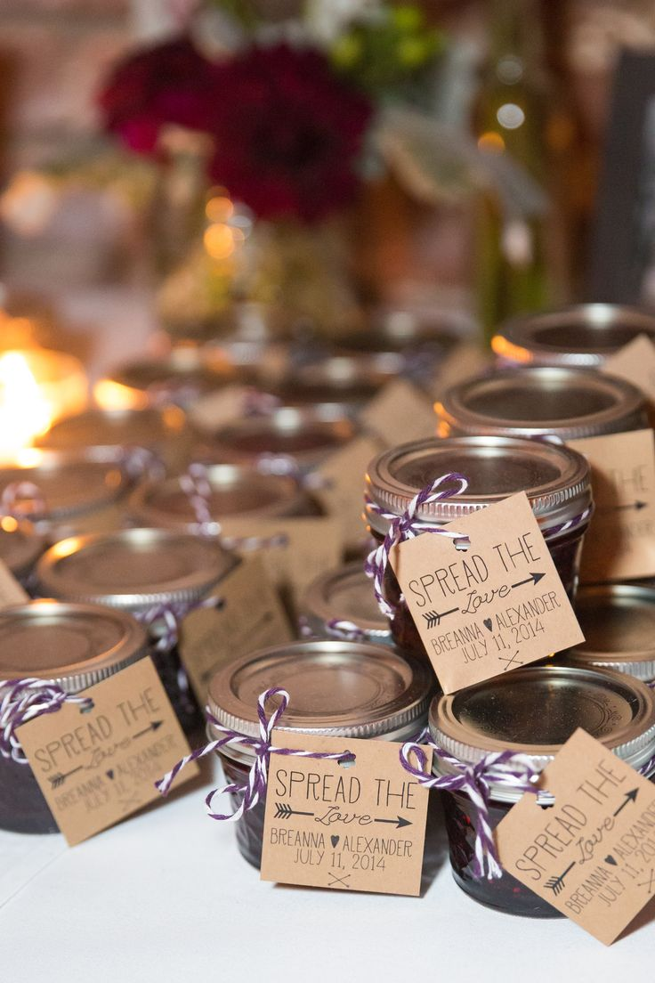 "Homemade triple berry jam was given to guests to take home. These were made by Breanna's stepmother and grandmother, who packaged the jams in small glass jars with kraft paper tags that read ""Spread the Love."""