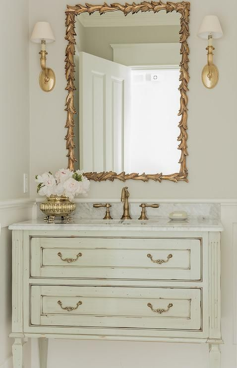 Light gray powder room with gold accents boast a light gray French washstand accented with gold pulls and a marble countertop with an antique brass faucet kit positioned beneath a gold leaves mirror flanked by gold sconces mounted on a light gray wall finished with wainscoting.