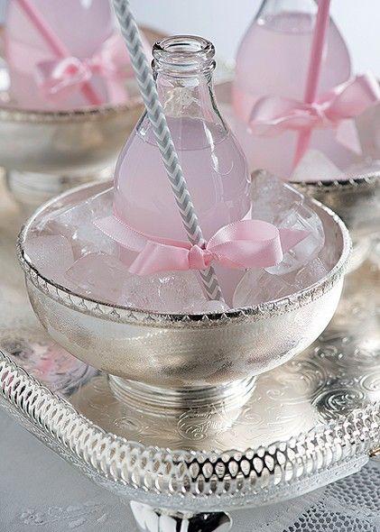 Bowls de prata com gelo servem de apoio para as garrafinhas. Além de deixar charmoso, o enfeite de laço rosa segura o canudo
