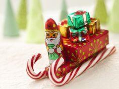 Santa's Candy Sleigh: Glue gun and glue sticks; 8 candy canes, 6 inches long; 4 bars (2.07 ounces each) chocolate-covered peanut, caramel and nougat candy; 4 packages (1½ ounces each) raisins; 4 foil-covered chocolate Christmas trees (1.3 ounces each) or 12 foil-covered chocolate gift packages; 4 foil-covered peanut butter or chocolate Santas (1 ounce each)