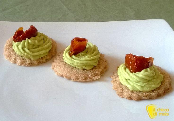 Tartine con crema di avocado e pomodori secchi. Ricetta per un antipasto facile e leggero per aperitivi fingerfoood e buffet: tartine con crema di avocado