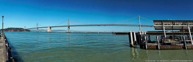 Oakland Bay Bridge, San Francisco, vue panoramique depuis le port - Le Oakland Bay Bridge est un pont autoroutier suspendu à deux niveaux, qui permet la traversée de la baie de San Francisco par l'Interstate 80, en passant par l'île de Yerba Buena (arrière plan sur la gauche), jusqu'à la ville de Oakland située sur l'autre rive.  San Francisco, Californie, USA