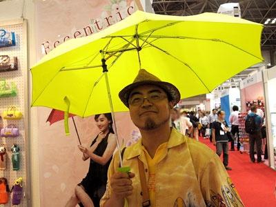 「偏心傘」    「Eccentric Umbrella」は、もしかしたら大きなブームを巻き起こすかもしれない。香港メーカーの製品で、漢字では「偏心傘」。つまり、取っ手が中心から外れた位置にある傘だ。傘は片手で持つため、体の中心からずれた位置に傘の中心が来てしまう。ということで取っ手の位置をずらし、片手で持っても傘の中心が頭の上に来るようにしている。