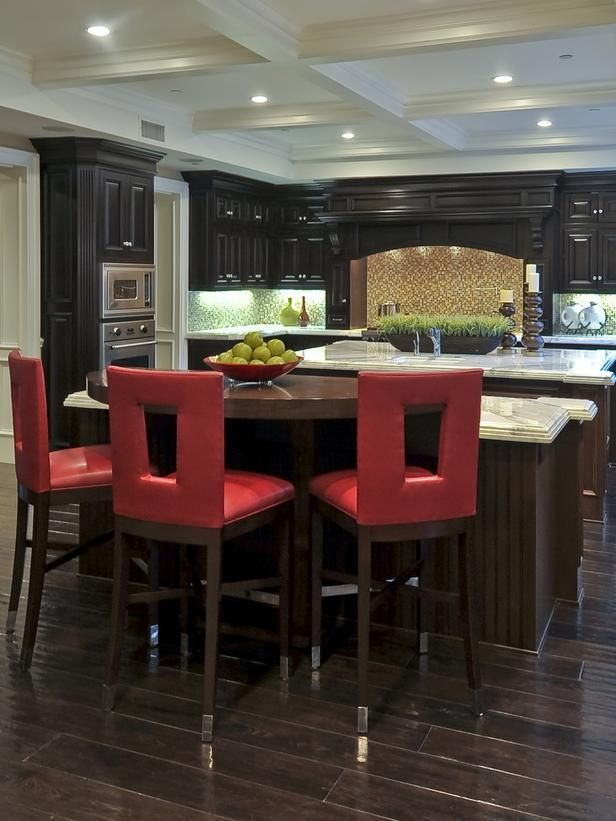 Red Hot Kitchen Nothing spices up a rich, gourmet kitchen quite like a playful pop of red. These colorful barstools are the perfect complement to dark wood cabinetry and floors in this Old World-inspired kitchen. White coffered ceilings, recessed lighting and white marble countertops help reflect light around the room, which visually expands the already spacious gathering spot.