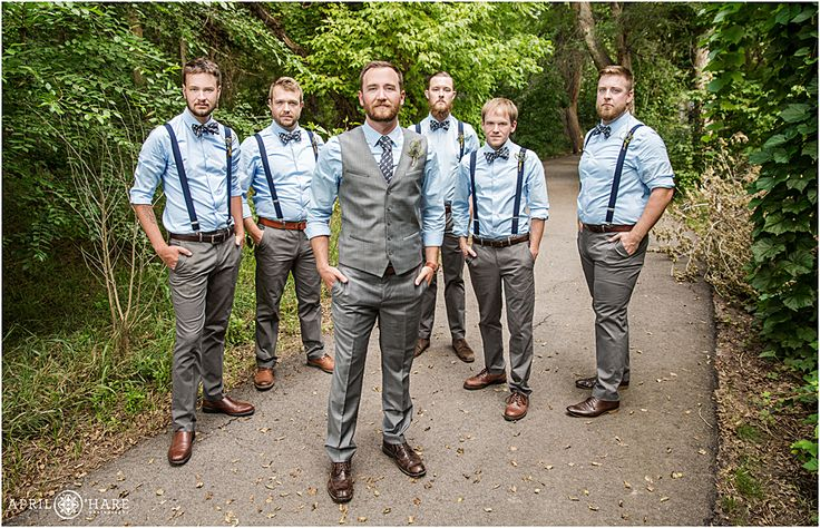 Groomsmen wearing suspenders and blue polka dot bowties pose with groom at Chatfield Botanic Gardens in Colorado.