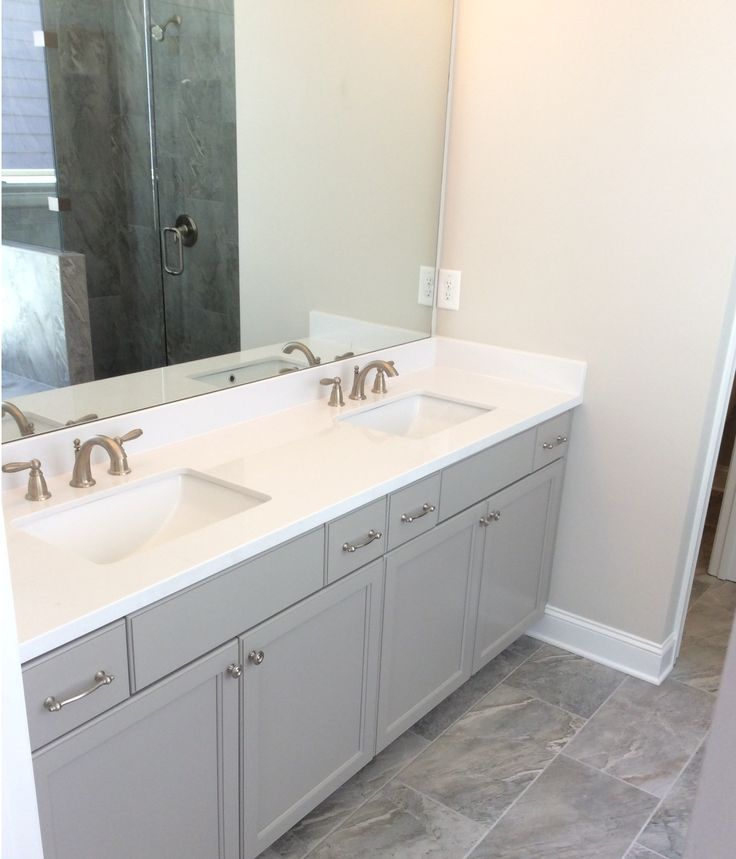 This Deerfield bathroom features our Wellborn cabinets in Dove and Karma Gray floor tile