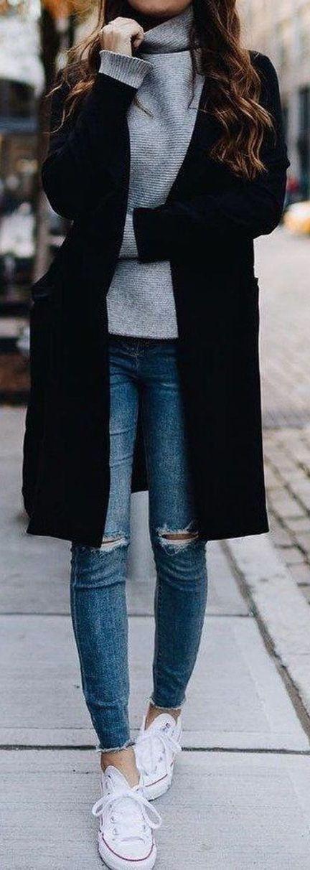 Schwarzer Mantel über grauem Rollkragenpullover und Jeans im Used-Look.