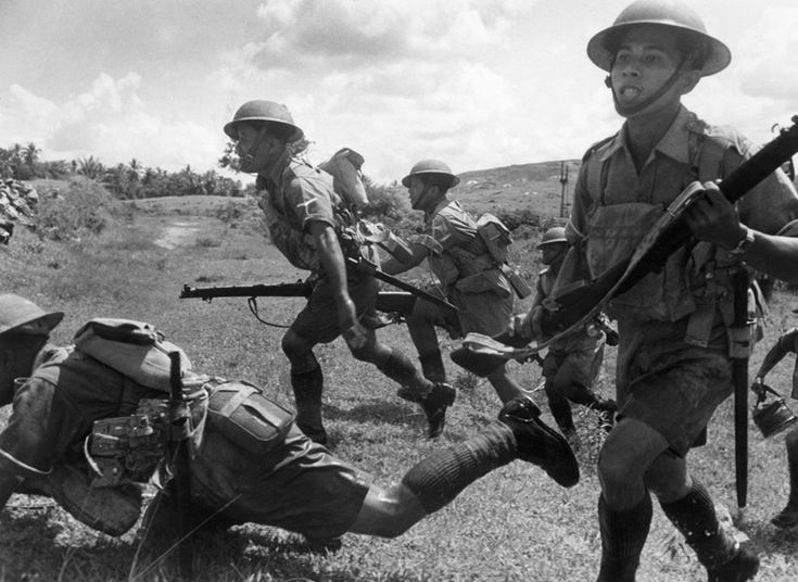 Allied Malayan soldiers intent on defending the Malay Peninsula against the Imperial Japanese Army charge forward in battle before the Japanese completed their occupation of the peninsula and pushed the Allies back onto Singapore Island. West Malaysia. 10 February 1942.