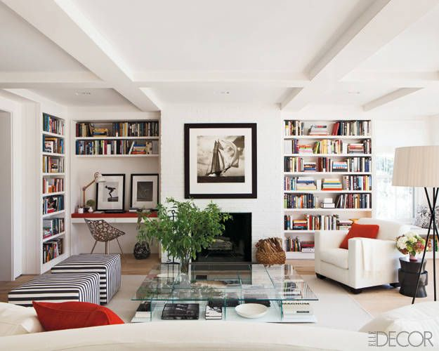 Library of a Nantucket house designed by Rebecca Ascher with Joshua Davis; ottomans by Antonio Citterio; linen-upholstered armchair by Christian Liaigre; cocktail table by Piero Lissoni; walls, brick fireplace and custom-made bookshelves coated in Country Stove White by Ralph Lauren Paint; floor lamp by Santa & Cole; steel chair by Philippe Starck; desk lamp from Design Within Reach