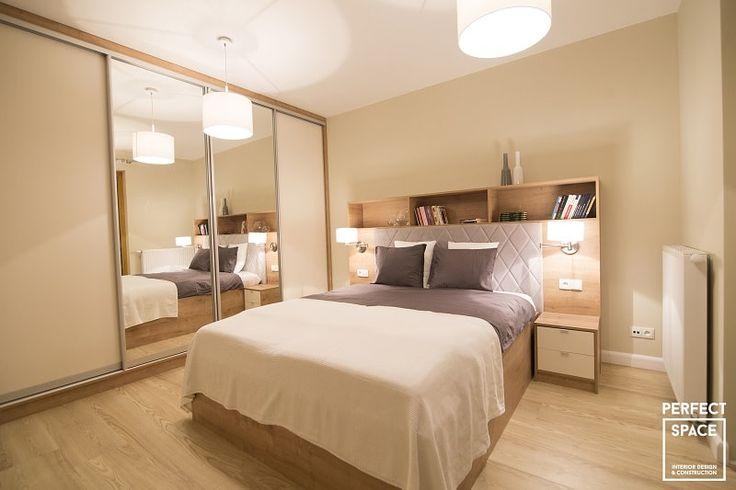 Przytulne wnętrze sypialni, z zabudowanym wezgłowiem łóżka służącym jako podręczna szafka i nocny stolik.