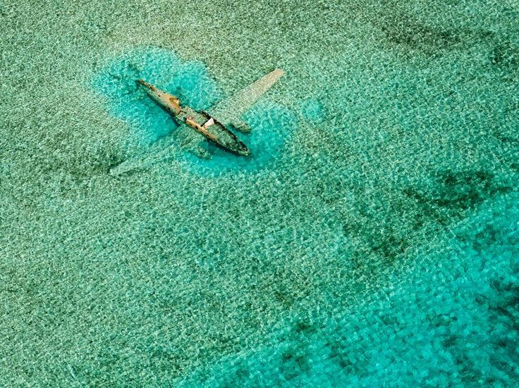 While island hopping around the Bahamas in a Cessna C172 aircraft, I made this aerial of a Curtiss C-46 that ditched on November 15, 1980. It crashed while it was on a drug smuggling mission for the Colombian Medellín drug cartel and lies in shallow water east of the Norman's Cay airport in the Exumas, Bahamas. My preflight Internet research paid off! - National Geographic