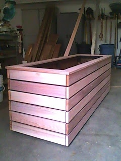 """bamboo planter 2' x 6' clear cedar outer, 1/2"""" pressure treated plywood creates inner structural.  bottom panel has landscape cloth over galvanized screen for drainage.  add rocks for counterbalance and plant with loose recycled grass clippings."""