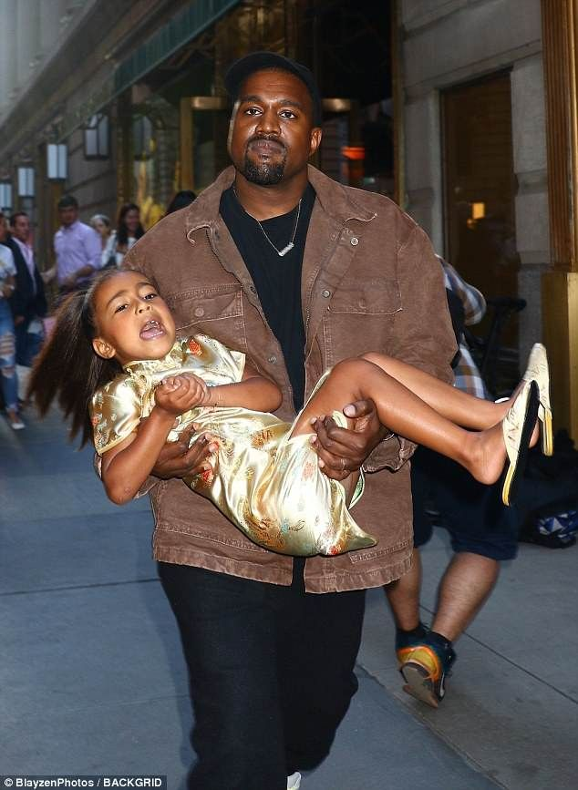 Kanye West carries unhappy looking North to her fifth