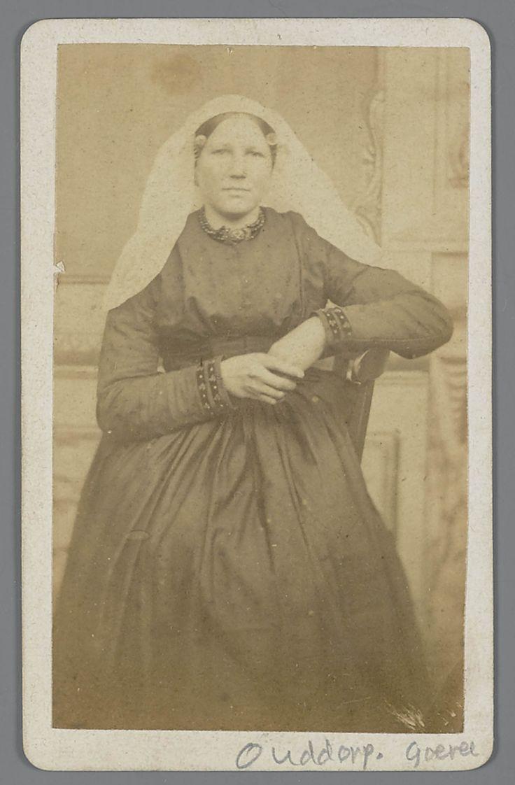 Vrouw uit Ouddorp, gekleed in de streekdracht van het eiland Goeree. Onder de sluiermuts draagt de een ondermuts met een oorijzer, met 'krulllen' aan de beide uiteinden. Boven de krullen is een paar mutsenspelden in de muts gestoken. #GoereeOverflakkee #ZuidHolland